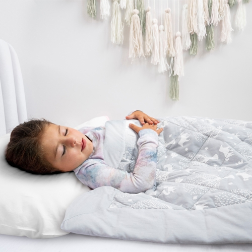 toddler girl sleeping in bed with toddler-bed weighted blanket