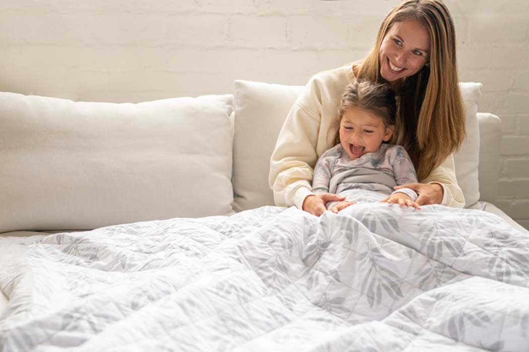 mom and little girl on couch under lounge weighted blanket