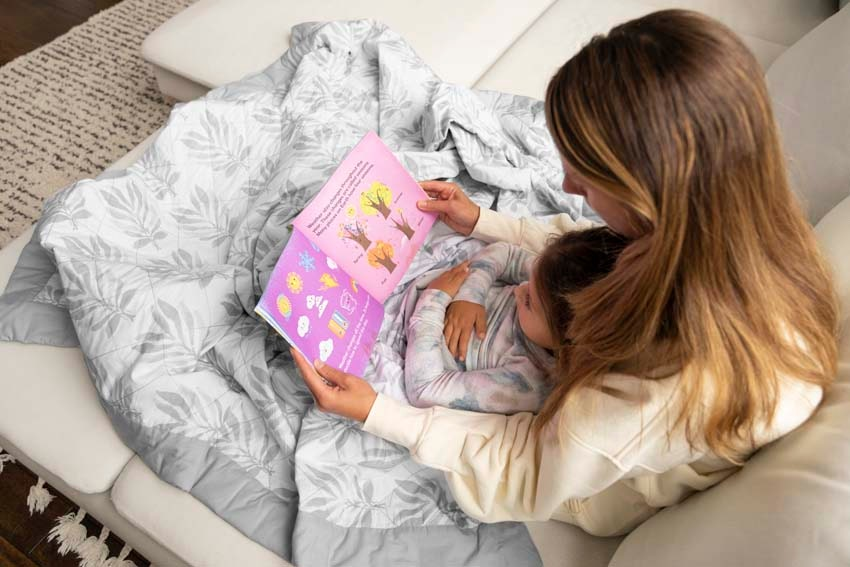 mom and toddler girl reading on couch under lounge weighted blanket
