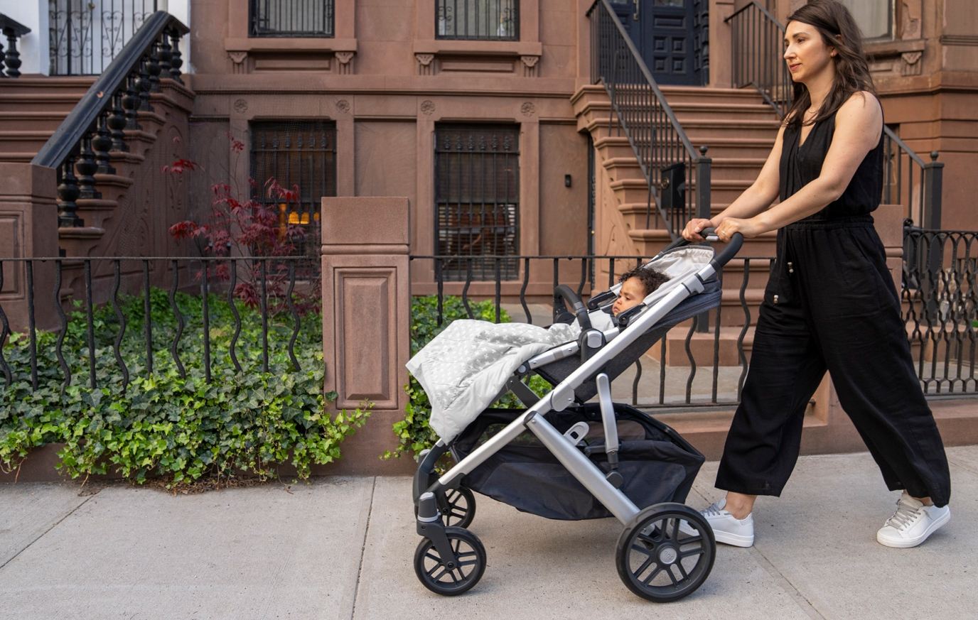 mom pushing baby in stroller with stroller weighted blanket