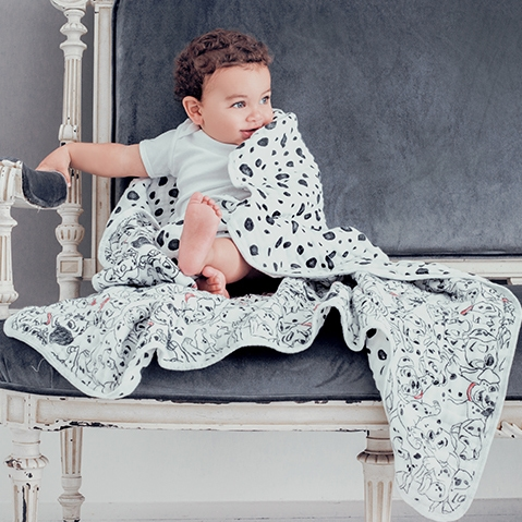 Swaddled baby sitting on a chair - Aden and Anais