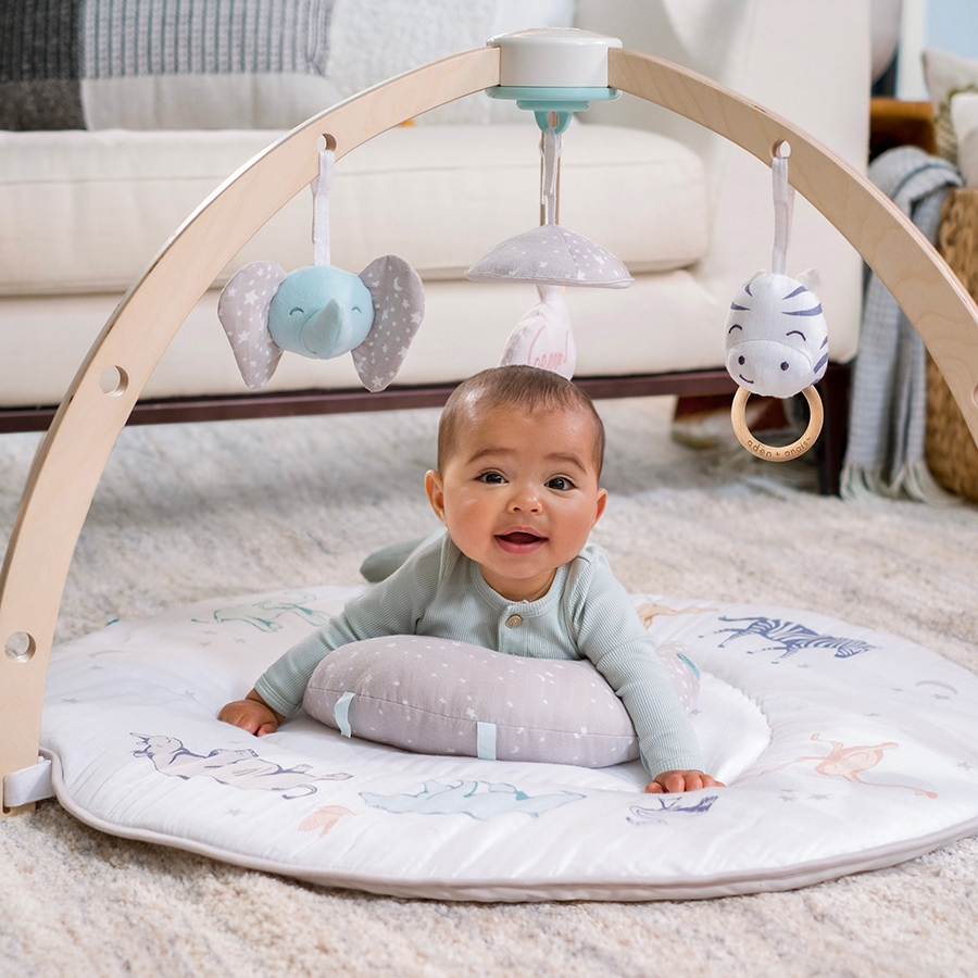 baby doing tummy time with tummy time pillow on aden + anais activity gym
