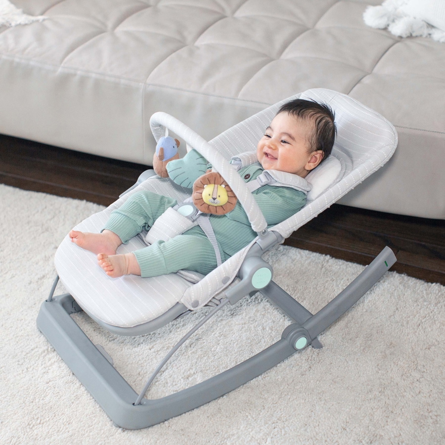 baby playing with toy bar on aden + anais bouncer + rocker + seat