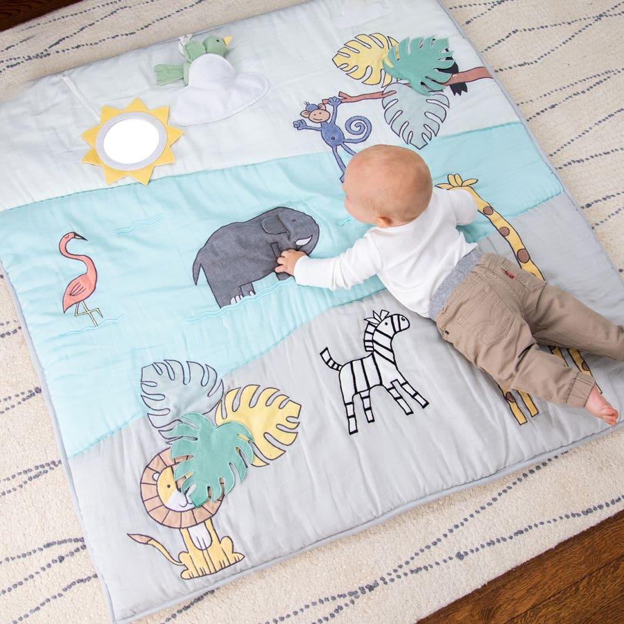 baby reaching for bird toy on bonding playmat