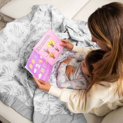 mom reading to daughter under lounge weighted blanket