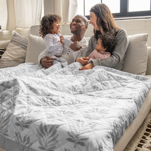 family laying on couch with lounge weighted blanket