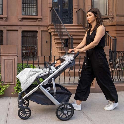 mom pushing baby in stroller with stroller weighted blanket on baby
