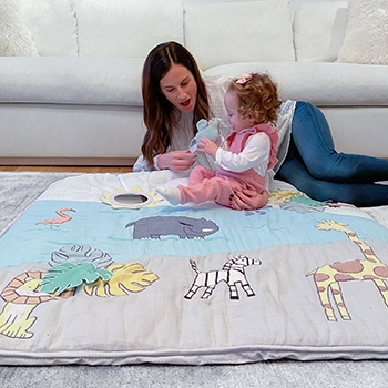 mom and baby playing on mat
