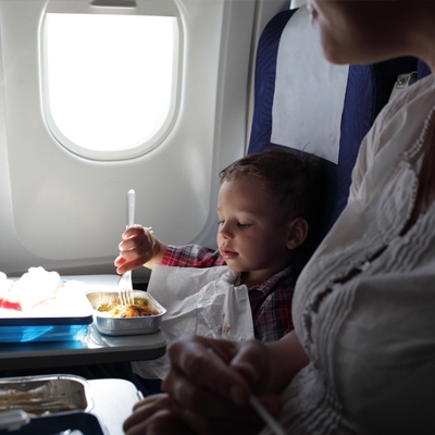 Little boy eating on an airplane