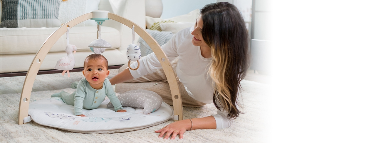 mom and baby doing tummy time with activity gym