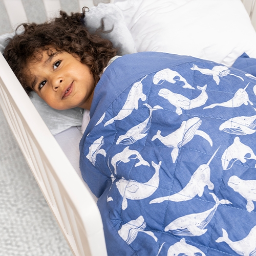 smiling little boy under toddler-bed weighted blanket