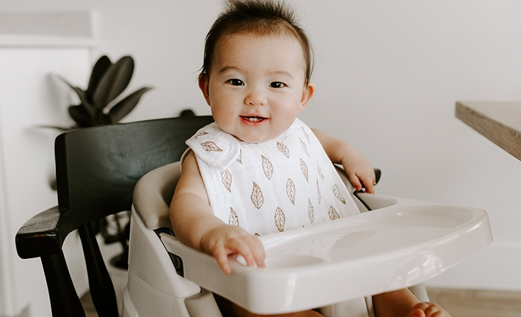Baby sitting on a high chair - Aden and Anais