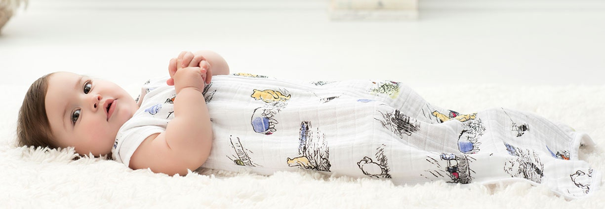 Baby laying on a rug in a sleeping bag