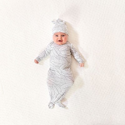 Baby wearing the comfort knit collection gown and hat, Zebra Plant