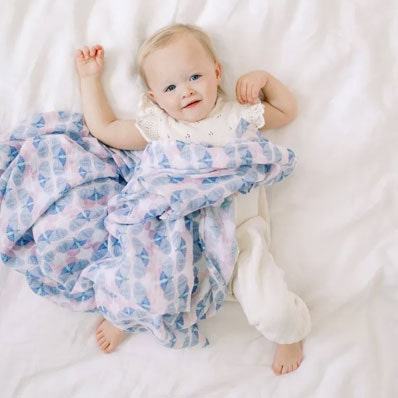 baby on bed with aden + anais cotton muslin swaddle deco