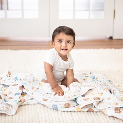 baby on ground with aden + anais winnie in the woods cotton muslin blanket