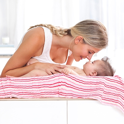 Swaddle blanket used to cover changing table surface while mother and baby is cuddling