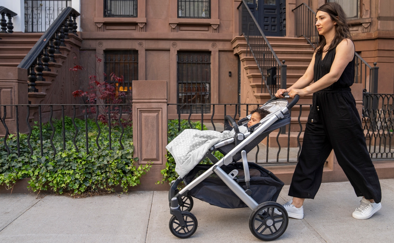 mom pushing baby in stroller with on-the-go weighted blanket
