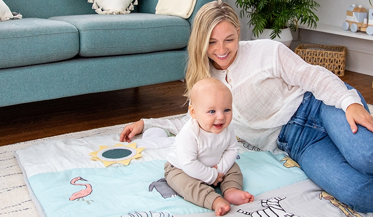 Smilling baby playing with mom on Aden and Anais playmat