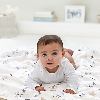 baby laying on her tummy on a swaddle