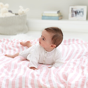 baby laying on swaddle