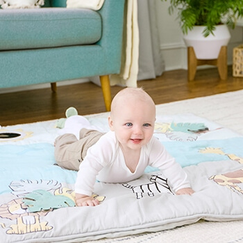 baby laying on play mat