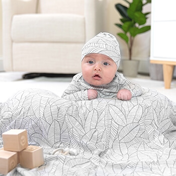 baby laying on pillow covered with a comfort knit swaddle